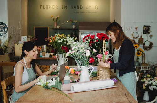 Happy women working with flowers and laptop