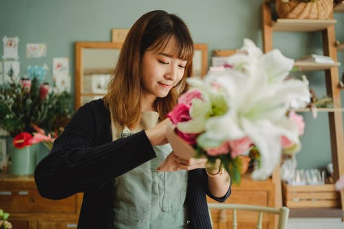 Smiling ethnic female florist in apron standing in floral shop and arranging bunch of fresh flowers