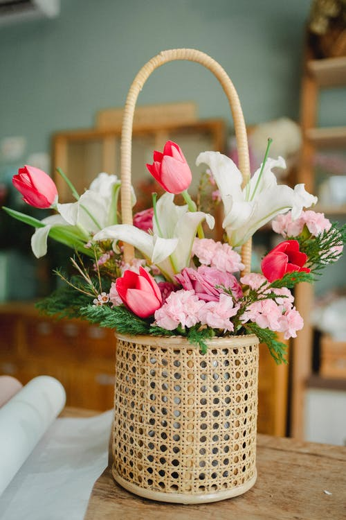 Wicker basket with fresh various flowers on wooden table in modern floral shop
