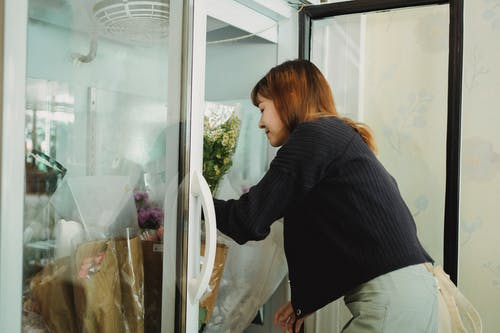 Young Asian woman putting flowers in cold