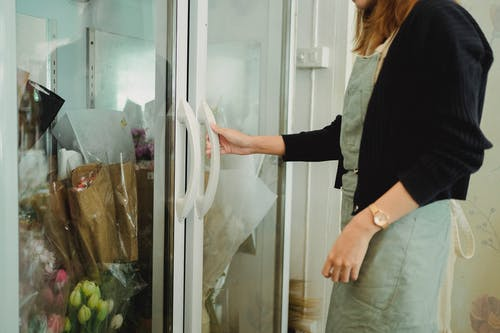Crop faceless female florist standing near fridge with various flowers while working in floral shop