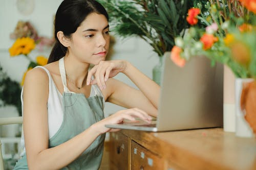Serious young woman working on laptop