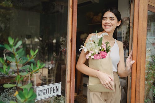Toothy smiling female standing near flower shop and holding paper package with bouquet