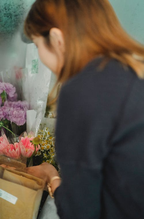 Side view of female florist choosing and taking ready made bouquet from box in floral shop