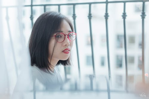 Side view of young attentive ethnic female in eyeglasses with red lips resting on fenced terrace and looking at camera