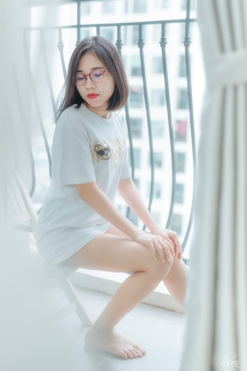 From above of young pensive barefoot ethnic lady in casual apparel and eyeglasses with makeup sitting on balcony while looking down