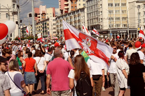 People Rallying on Street With Flags