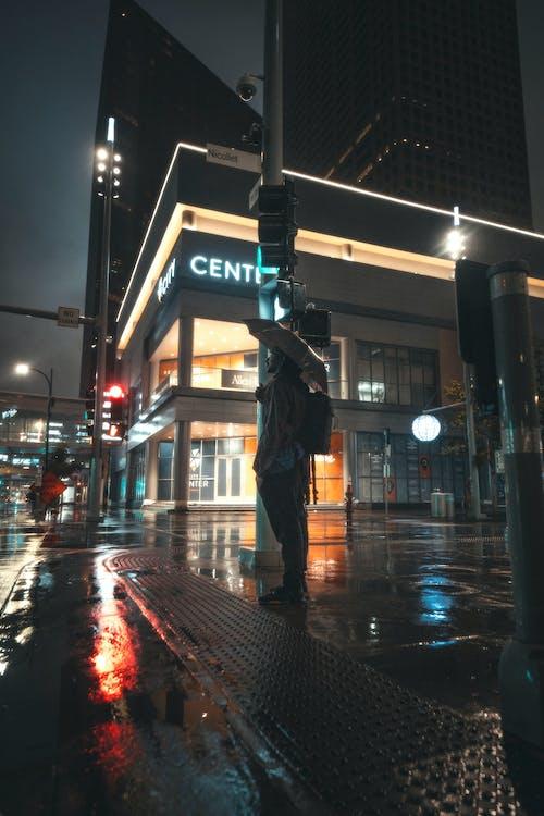 Man in Black Jacket and Black Pants Standing on Sidewalk during Night Time