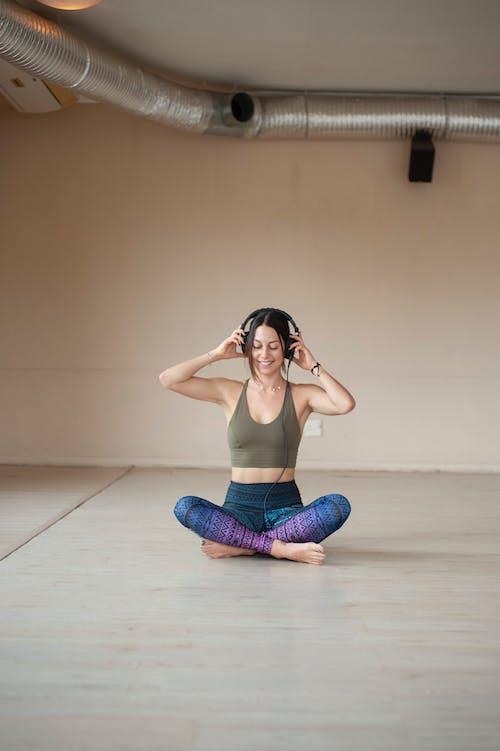Woman in Brown Tank Top and Purple Leggings Sitting on Floor