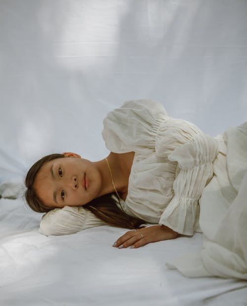 Tranquil young Asian female lying on white blanket in morning