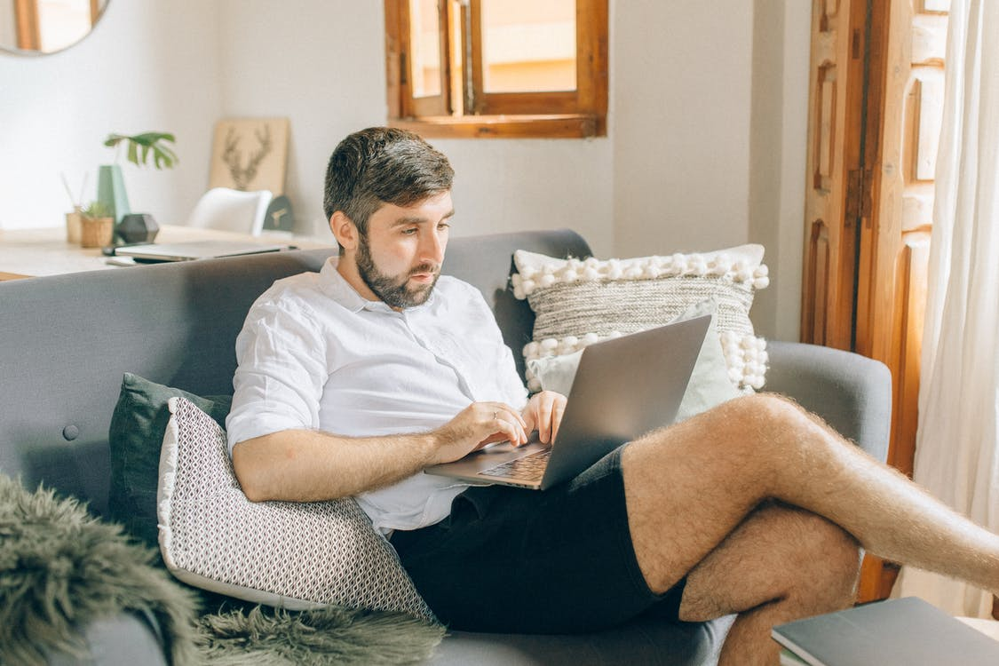 Man in White Polo Shirt and Black Shorts Sitting on Gray Couch Using Macbook