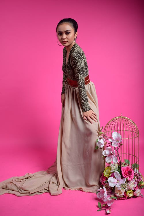 Elegant ethnic woman standing near cage