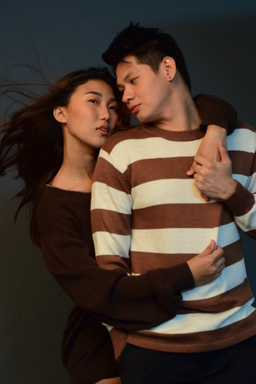 Loving ethnic man and woman in casual clothes hugging in studio while standing on gray background with flowing hair inside