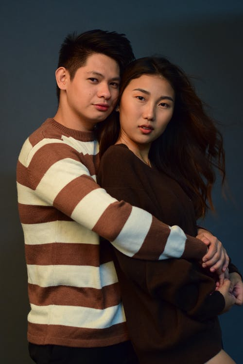 Romantic ethnic boyfriend and girlfriend wearing casual outfit hugging while standing on gray background and looking at camera in studio
