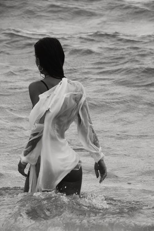 Black and white of anonymous female with dark hair in wet white shirt standing in waving sea