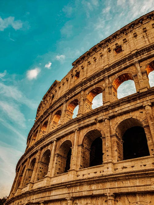 Low angle of ancient Coliseum with arched elements and stone columns under blue sky in Rome