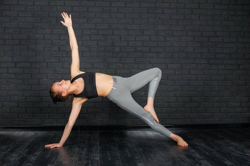 Full body of concentrated female in activewear standing in Side Plank Tree position in sports studio