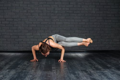 Athletic woman practicing Two Legged Sage Koundinya pose