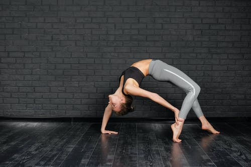 Flexible woman practicing Urdhva Dhanurasana in studio