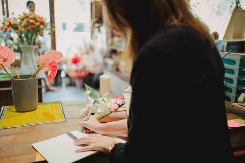 Back view of anonymous florist writing in notebook while working in floral shop in daytime