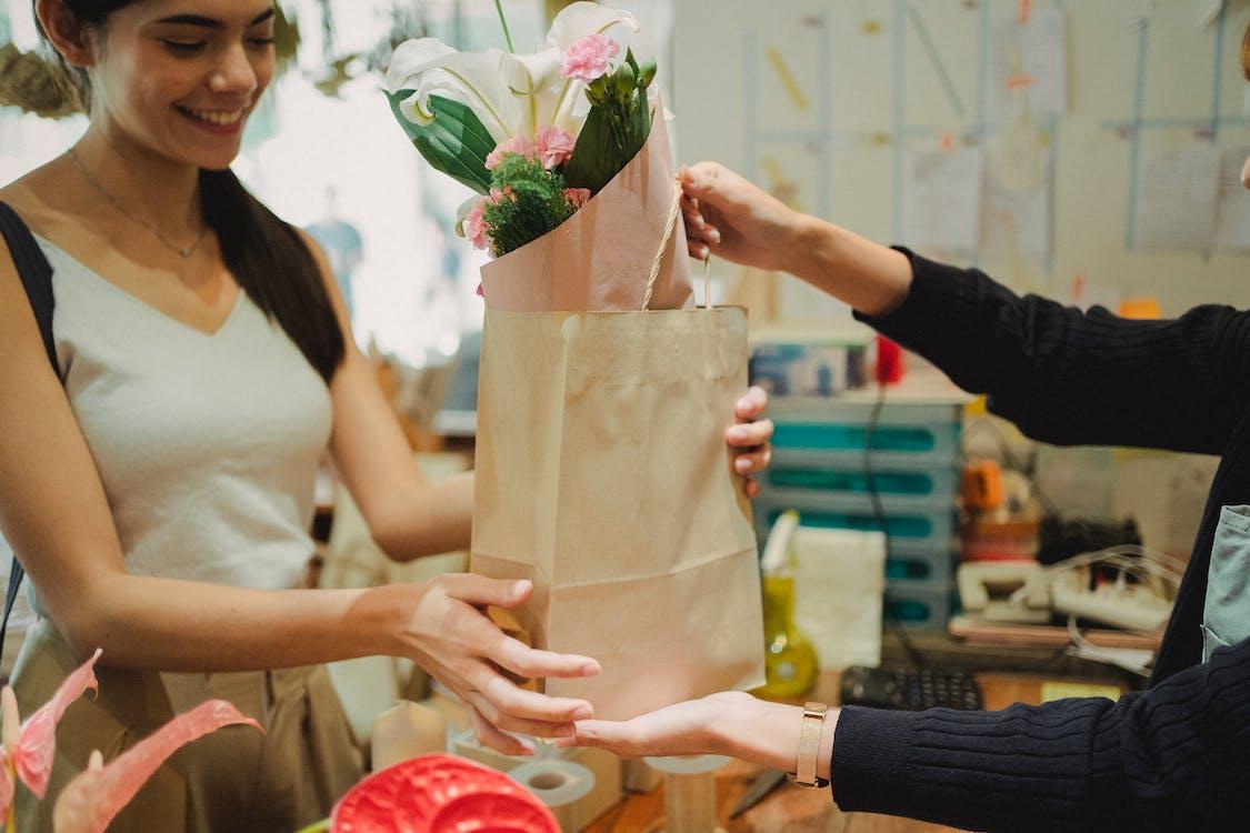 Flower shop assistant passing bag with bouquet