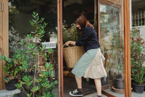 Side view of Asian female florist in casual clothes carrying basket with flowers into shop