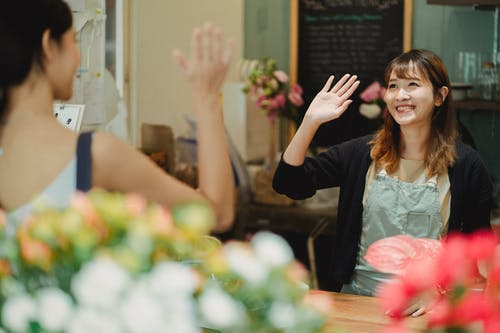 Positive Asian woman greeting client waving hand while working as florist in flower shop