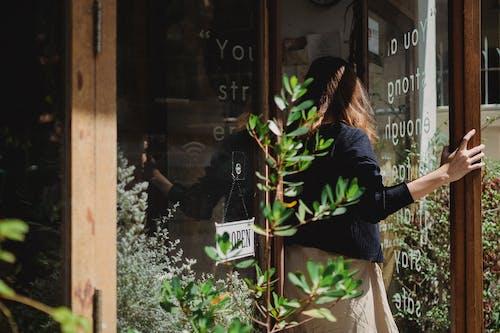 Woman closing door into flower shop