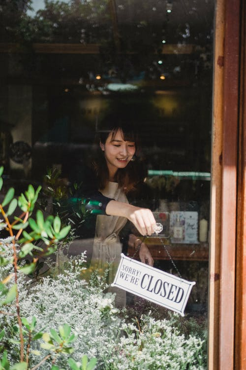Ethnic woman in casual clothes hanging up sign on door after end of workday