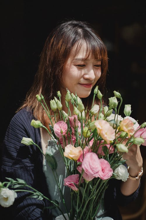 Happy woman holding bouquet of flowers