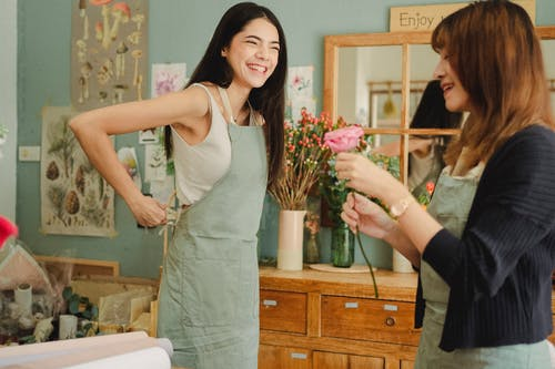 Positive female florists in uniform having conversation and laughing while working in flower shop