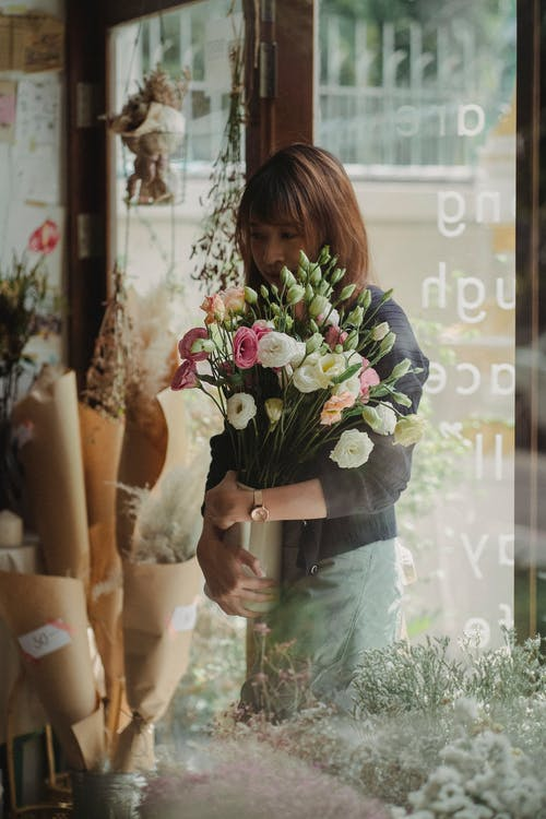 Through glass woman carrying vase with blossom flowers while standing near entrance in shop
