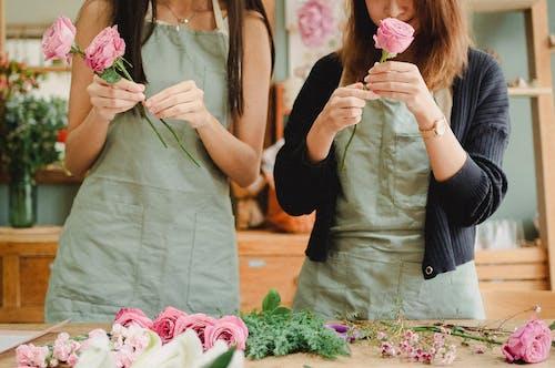 Female florists arranging bouquet of roses