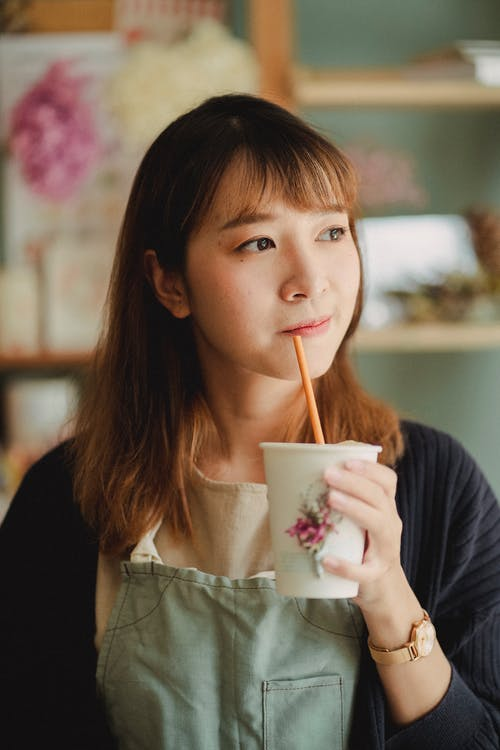 Calm Asian woman in casual clothes looking away enjoying paper cup of delicious coffee with tube