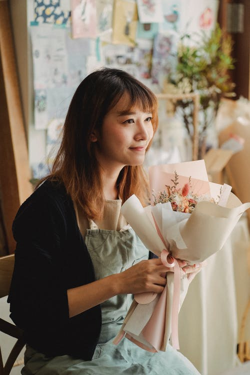 Smiling florist with bouquet of gorgeous flowers