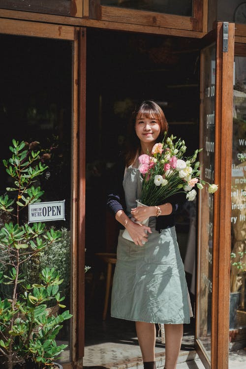 Young Asian female in apron looking at camera while holding bouquet of flowers standing at shop entrance