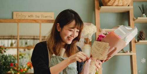 Positive Asian female in casual clothes and apron making bouquet of fresh flowers and smiling in cozy room