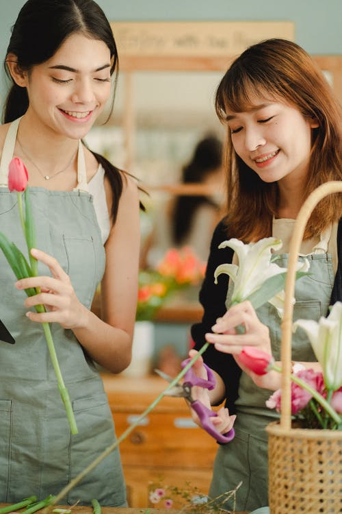 Smiling florists in casual clothes and aprons making composition with fresh flowers while spending time at workshop
