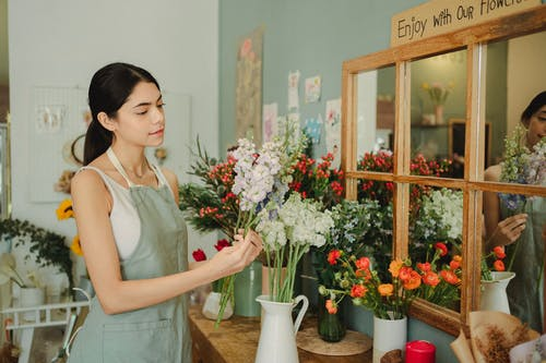 Florist  standing near counter with flowers