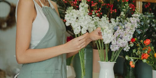 Crop anonymous florist in apron standing near table with flowers in vases and choosing flowers for composition