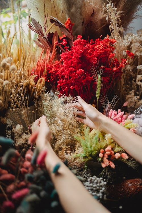From above of crop anonymous female touching bouquet of dried flowers while decorating counter of floristry store