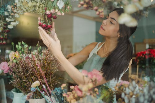 Young slim female florist in light apron touching decorative flowers in hands and standing in fragrant floral shop