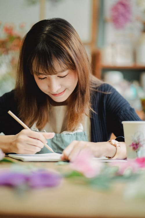 Positive Asian woman writing in notebook in light room