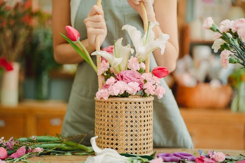 Crop anonymous female florist in light green apron standing with aromatic lily and tender pink tulips bouquet arranged in wicker basket in sunny floral shop