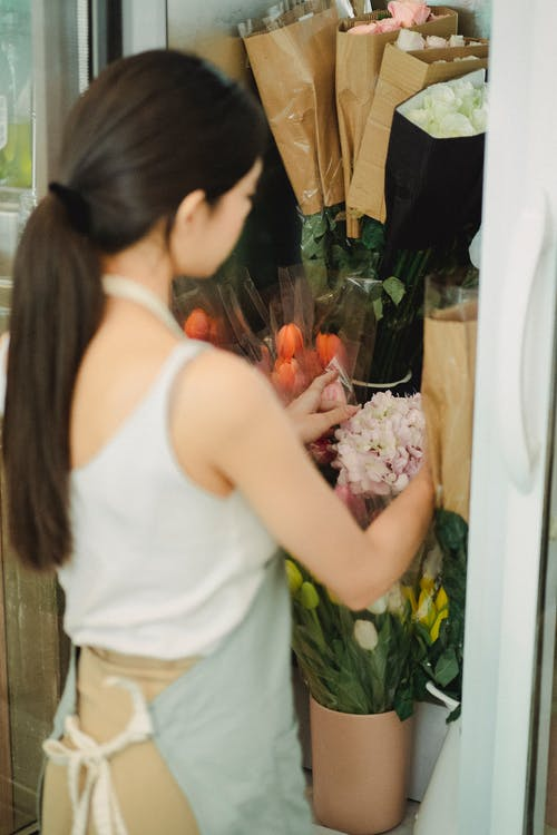 Faceless woman holding flowers in fridge floral shop