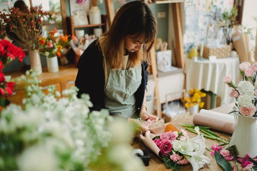 Concentrated young female florist in uniform standing near counter and arranging bouquet while working in light floral shop