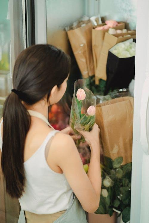 Unrecognizable florist taking flowers out of fridge in shop