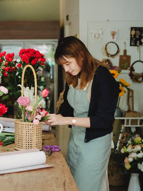 Content young Asian florist wearing light green apron arranging flowers in wicker basket while working in floristry studio