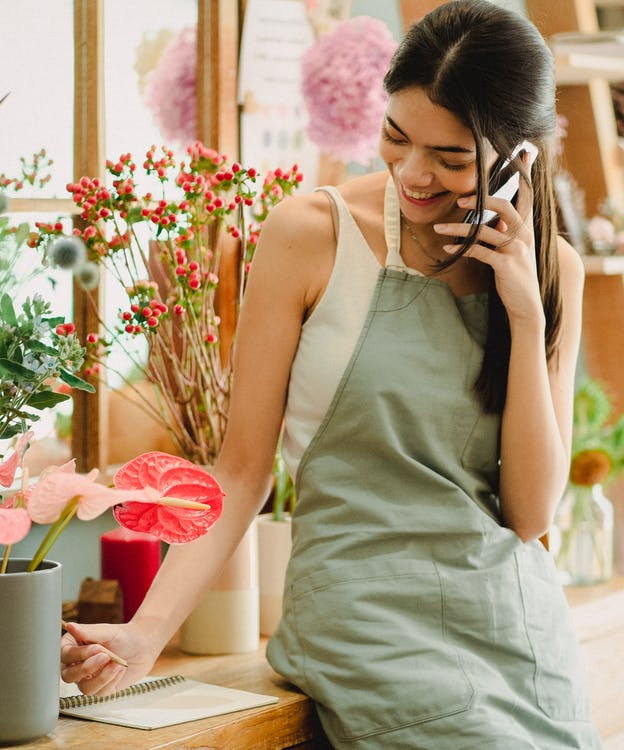 Floristería Mujer Sonriente Hablando Por Teléfono En La Tienda De Floristería
