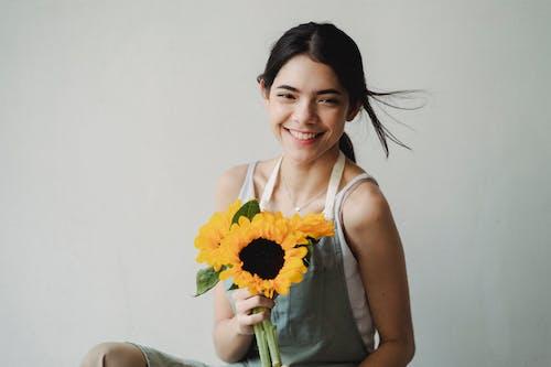 有向日葵束的快樂的婦女站立在輕的演播室